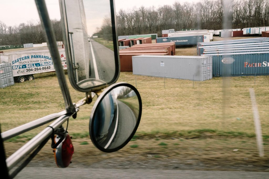 Virginia - 4/2/2015 - A storage lot for semi trailers along Interstate 81 is seen through the side window of Robert Harsell's 1989 Freightline semi tractor rolls down Interstate 81 in rural Virginia. Harsell (68) is part of a dwindling population of independent owner/operators in an economy that is steadily becoming more corporate. He feels that new safety regulations threaten their livelihood, and actually make highways more dangerous.